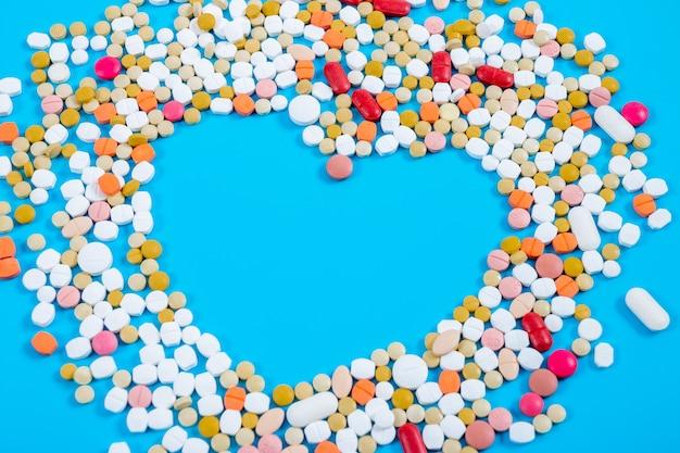 De nombreuses pilules sous la forme d'un coeur multicolore sur fond bleu