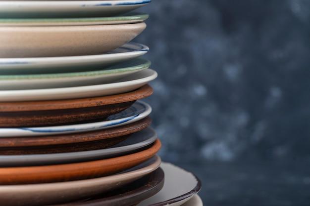 De nombreuses plaques en céramique vide de couleur sur fond noir, gros plan.