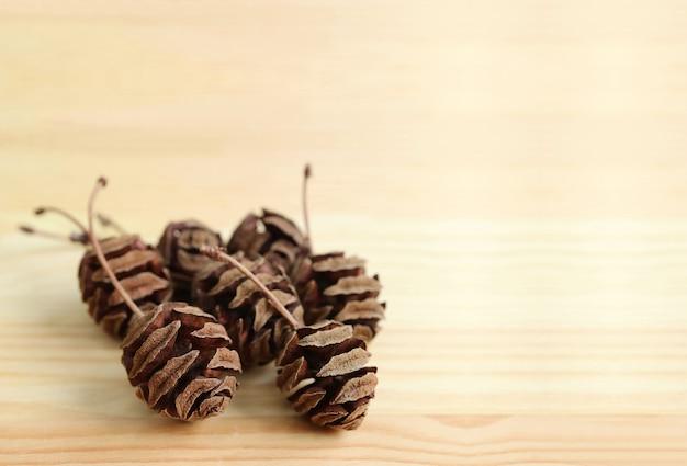 Nombreuses pommes de pin minces sèches et naturelles sur une table en bois brun clair avec un espace libre pour la conception