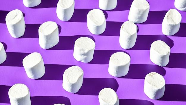 De nombreuses rangées de guimauves blanches de forme cylindrique se trouvent sur fond violet. modèle de malbouffe malsaine. modèle de bonbons