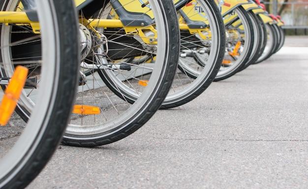 De nombreuses roues de vélos garés sur un parking à vélos.