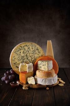 De nombreuses sortes de fromages sur une planche de bois avec des noix et du miel