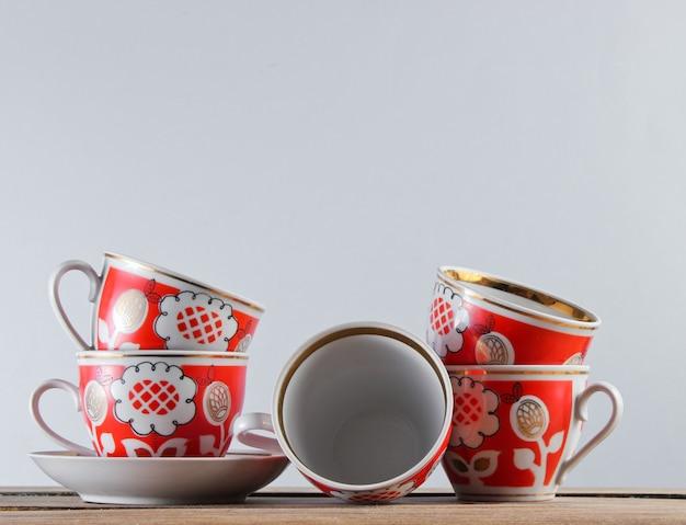 De nombreuses tasses en céramique antiques sur une table en bois contre un mur blanc