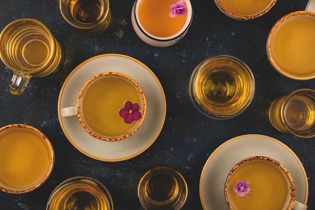 De nombreuses tasses de thé avec des fleurs violettes sur fond bleu foncé. disposition de la vue de dessus
