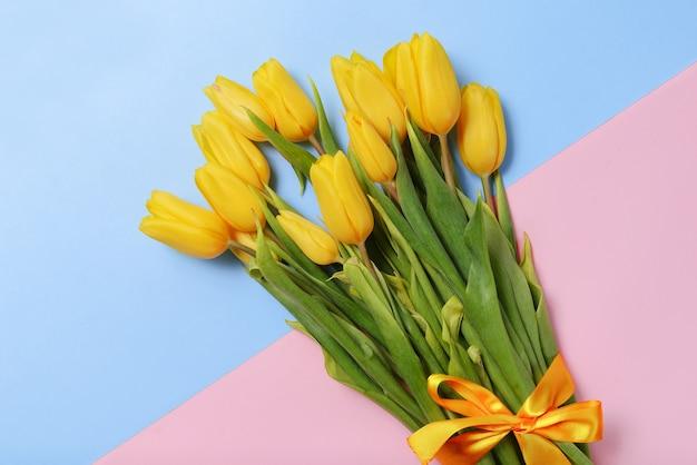 De nombreuses tulipes aux pétales jaunes sur une surface bleue, rose, un bouquet de fleurs