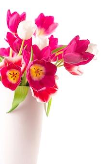 De nombreuses tulipes avec des feuilles dans un vase isolé sur une surface transparente