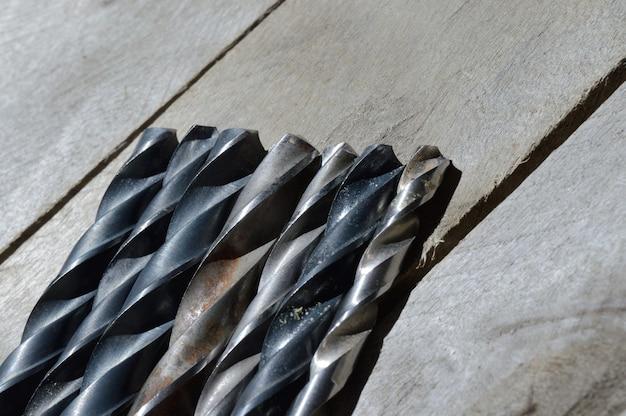 De nombreuses vieilles perceuses se trouvent sur un fond en bois de planche. fermer.
