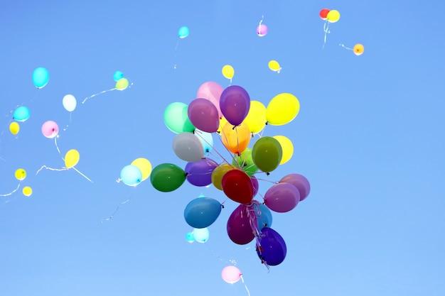 De nombreux ballons multicolores volant dans le ciel bleu. articles pour célébrer des événements