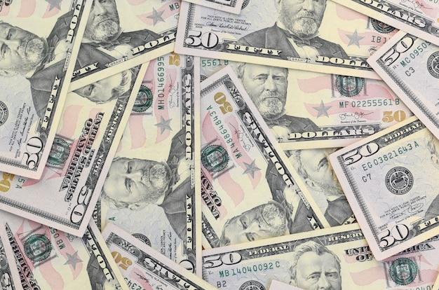 De nombreux billets de cinquante dollars américains sur une surface de fond plat se bouchent. vue de dessus plate. concept d'entreprise abstrait