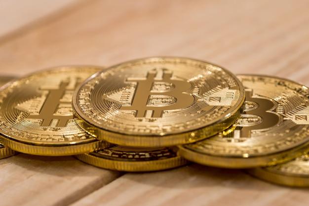 De nombreux bitcoins sur un bureau en bois. clsoe up