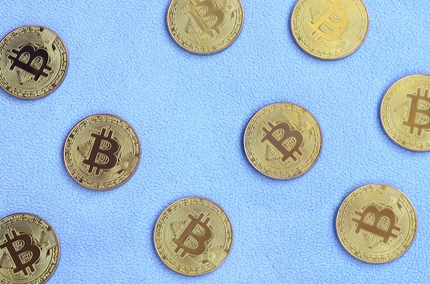 De nombreux bitcoins dorés reposent sur une couverture en polaire doux et moelleux bleu clair