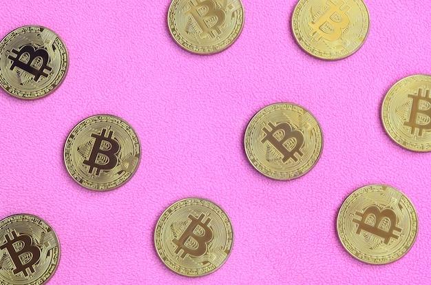 De nombreux bitcoins dorés reposent sur une couverture en polaire doux et moelleux rose pâle