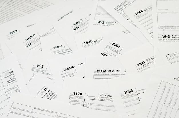 De nombreux blancs de formulaires fiscaux se trouvent sur la table de près. concept de routine et de bureaucratie de paperasse de contribuables