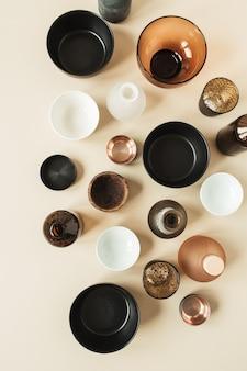 Nombreux bols, récipients, soucoupes sur beige pastel. mise à plat, vue de dessus de décorations en bois, céramique, verre.