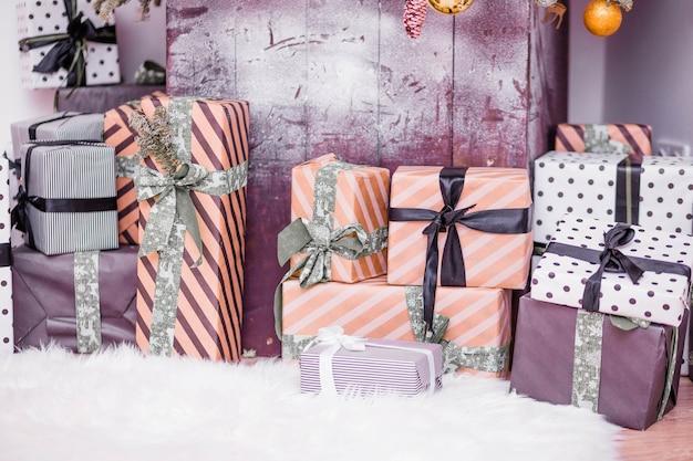De nombreux cadeaux sont sur le tapis de fourrure sous l'arbre