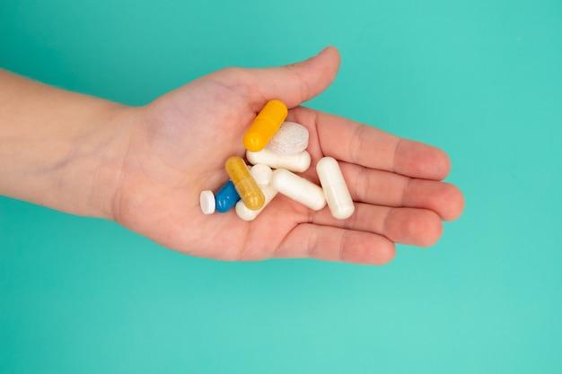 De nombreux comprimés dans la main d'un enfant doivent être pris sur fond bleu