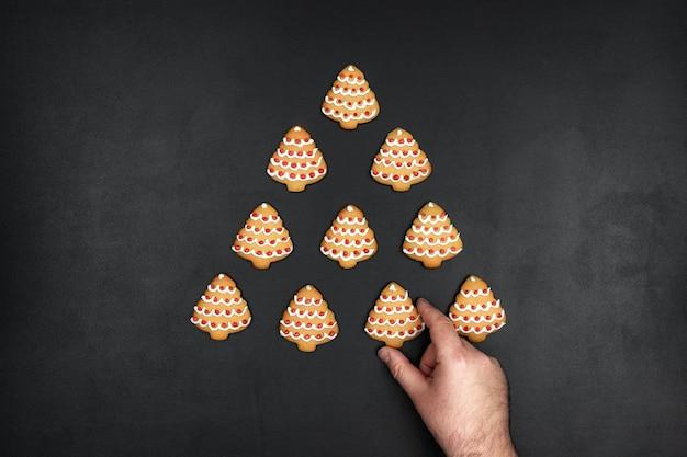 De nombreux cookies en forme de sapin de noël sur un fond de tableau noir, concept de nouvel an minimaliste avec une main