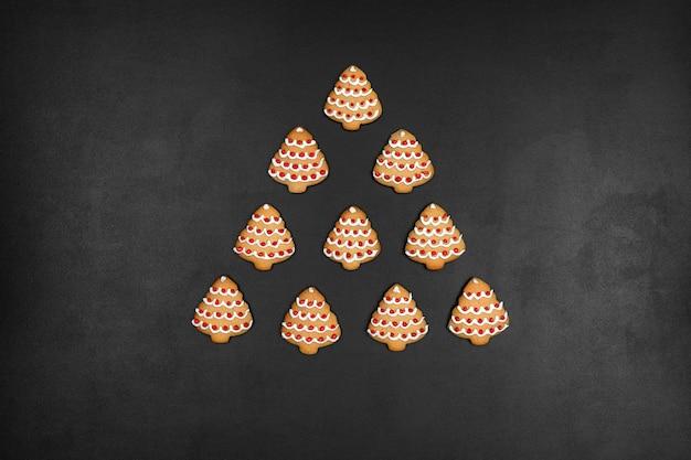 De nombreux cookies en forme de sapin de noël sur un fond de tableau noir, concept de nouvel an minimaliste