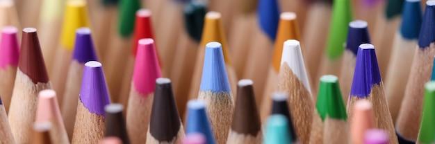 De nombreux crayons en bois pointus multicolores closeup background