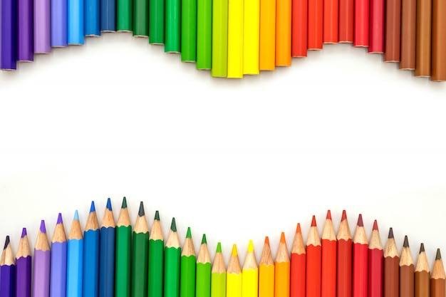 De nombreux crayons de couleur sur fond coloré