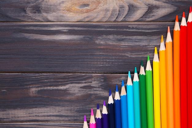 De nombreux crayons de couleurs différentes sur une table en bois
