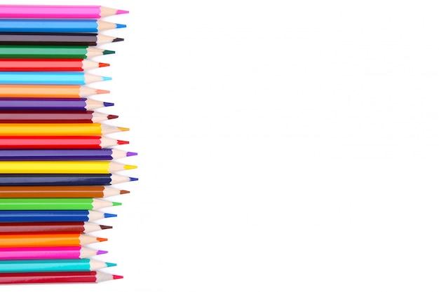 De nombreux crayons de couleurs différents sont isolés sur blanc