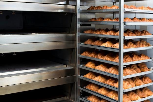 De nombreux croissants tout juste cuits au four dans un four de boulangerie