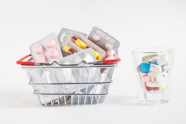 De nombreux emballages de pilules dans le panier et un verre sur fond blanc