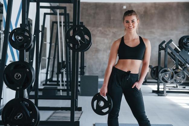 De nombreux équipements. superbe femme blonde dans la salle de gym pendant son week-end