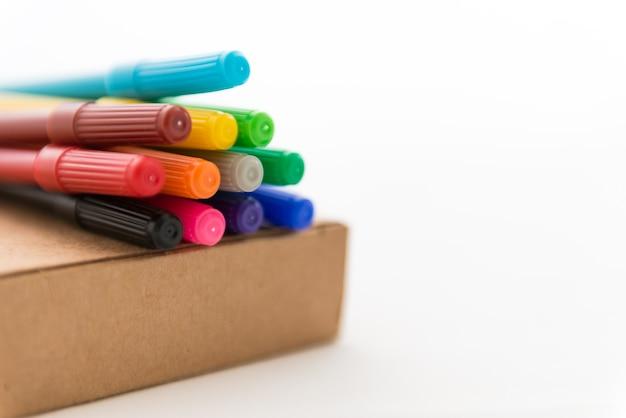 De nombreux feutres colorés sur une boîte en papier marron
