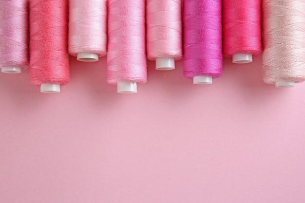 De nombreux fils à coudre sur fond de couleur rose