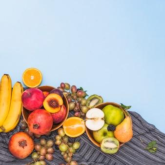 Nombreux fruits tropicaux sur textile à rayures sur fond bleu