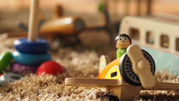 De nombreux jouets en bois pour bébés colorés sur un tapis de couleur marron clair qui comprennent un bus d'avion à billes et d'autres