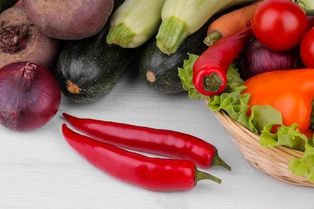 De nombreux légumes différents dans le panier sur une surface en bois blanche