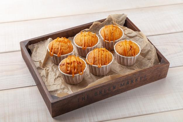 De nombreux muffins au caramel sucré sur planche de bois
