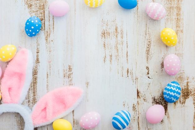 De nombreux œufs de pâques avec des oreilles de lapin sur une table en bois