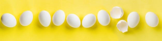 De nombreux œufs de poule blancs se trouvant en ligne sur une table à la mode jaune. composition créative minimale de pâques avec espace de copie. vue de dessus.