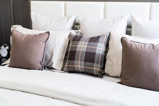 Nombreux oreillers sur lit blanc
