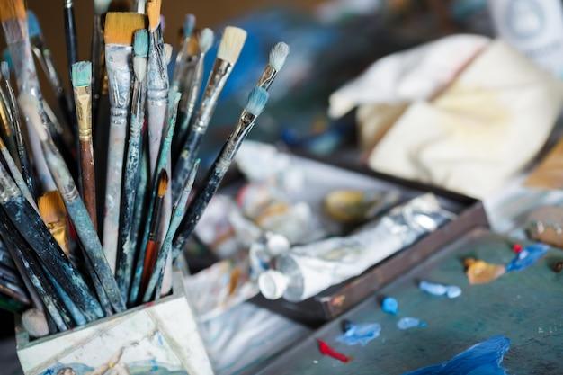 De nombreux pinceaux différents dans l'espace de travail de l'artiste