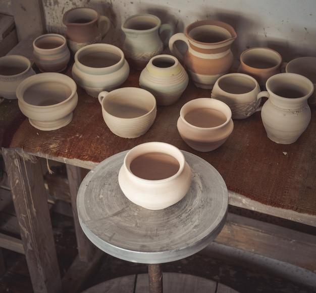 De nombreux pots en argile sont sur la table en poterie