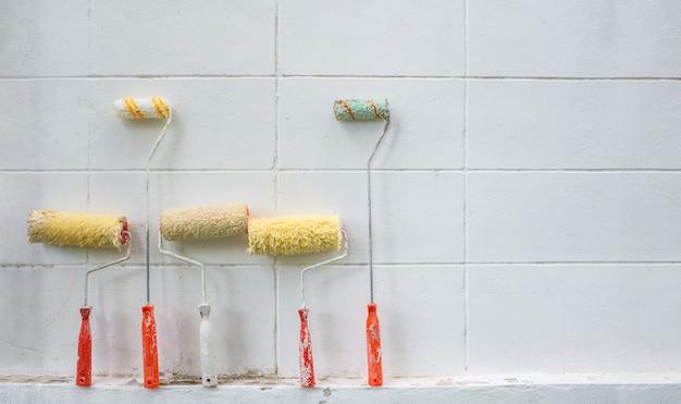 De nombreux rouleaux de peinture utilisés mis sur le ciment wal