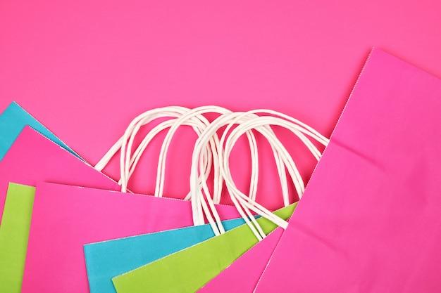 Nombreux sacs à provisions rectangulaires en papier multicolore avec poignées blanches