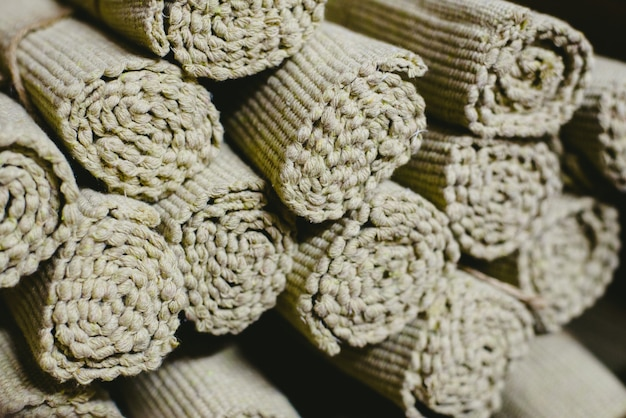 De nombreux tapis marron roulés dans un entrepôt à vendre.