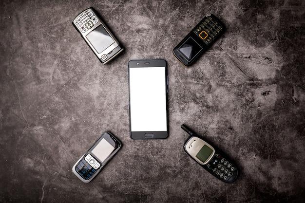 De nombreux téléphones portables obsolètes et un smartphone sur un fond grunge.