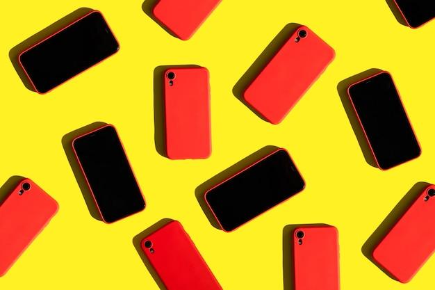 De nombreux téléphones portables rouges sur fond jaune modèle de communication et de gadgets