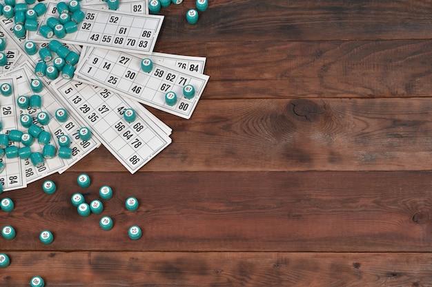 De nombreux tonneaux avec des numéros et des cartes pour le loto ou le jeu de table de bingo russe sur une surface en bois. le loto russe a des règles similaires au jeu de bingo mondial classique