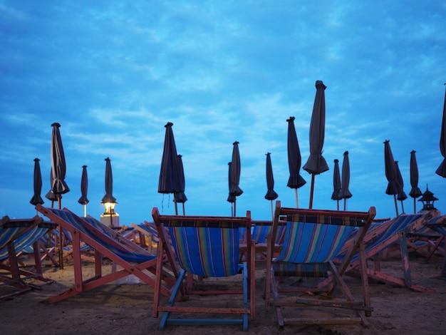 Nombreux transats en bois et parasols sur le sable
