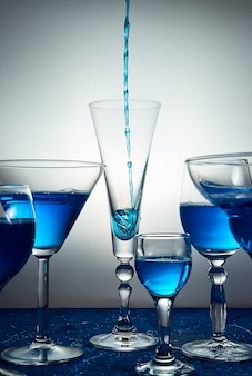 Nombreux verres à champagne bleu ou cocktail.