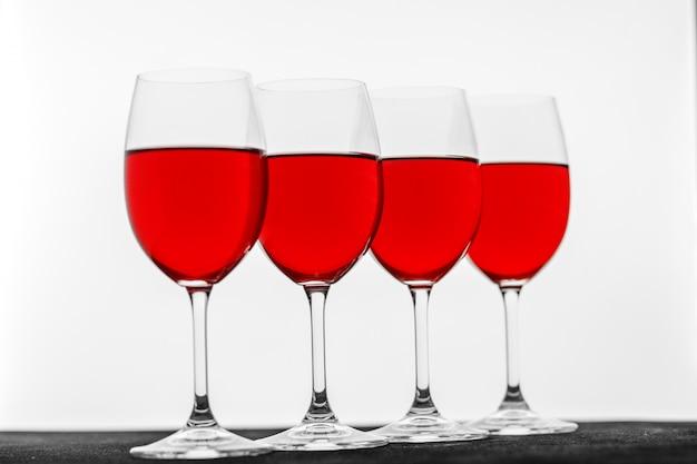De nombreux verres de vin français rouge sur fond blanc.