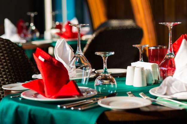 Nominations de table joliment décorées avec un beau décor avec des assiettes et des serviettes. l'élégante table à dîner
